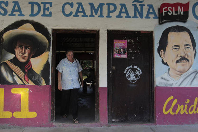 A woman walks past murals of Nicaragua's President Daniel Ortega (r.) and Nicaraguan revolutionary and Sandinista leader Augusto Cesar Sandino in Catarina November 4. President Ortega's ruling Sandinista National Liberation Front party will seek to change the constitution by year-end to remove presidential term limits.