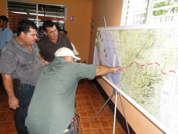 Three farmers study the route for the interoceanic canal on a map of Nicaragua, which the Chinese firm HKND Group presented in the southern city of Rivas during a meeting with people who will be affected by the mega-project. Credit: José Adán Silva/IPS