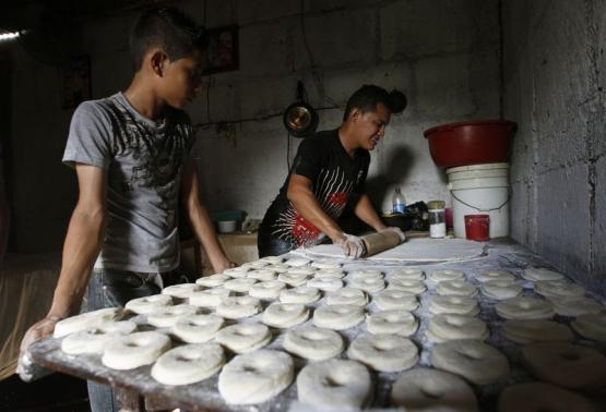 Victor Toruno (R) makes doughnuts with Francisco Jimenez at Toruno's home, which also serves as a bakery, in the Hialeah neighborhood in Managua August 13, 2014. Credit: REUTERS/Oswaldo Rivas