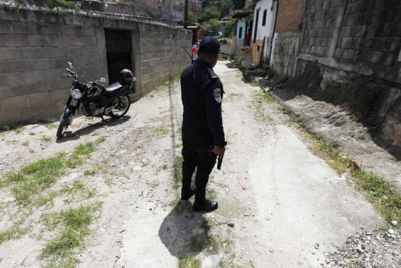 A police officer holds his gun while patrolling in the 14 de Marzo neighborhood, which most people have left due to gang threats according to local media, in Tegucigalpa August 25, 2014.  REUTERS/Jorge Cabrera