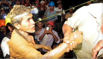 Miners and rescue workers hold a miner covered in mud after he was rescued from a gold mine blocked by a landslide in Bonanza, Nicaragua, Aug. 29, 2014.