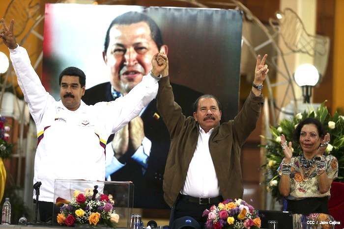 Nicolas Maduro (left) and Daniel Ortega holding their hand in the air, while Rosario Murillo (right) stands beside her husband, with a photo of Hugo Chaves in the background. Undated photo from El19digital.com