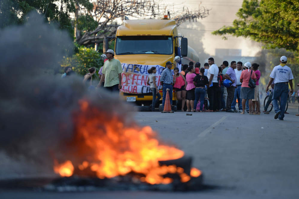 People protest burning tires against the inauguration of the works of an inter-oceanic canal in Rivas, Nicaragua on December 22, 2014. Chinese company HKND Group launched work Monday on a $50 billion canal across Nicaragua, an ambitious rival to the Panama Canal that skeptics dismiss as a pipe dream and protesters say will wreck the environment. AFP PHOTO / STR